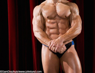 Cropped picture of a professional body builder standing on a stage flexing his arm, chest, and abdominal muscles. Picture is cropped from mid thigh to shoulders. Massive shoulder muscles. Fantastic abs. Hands clasped in front.